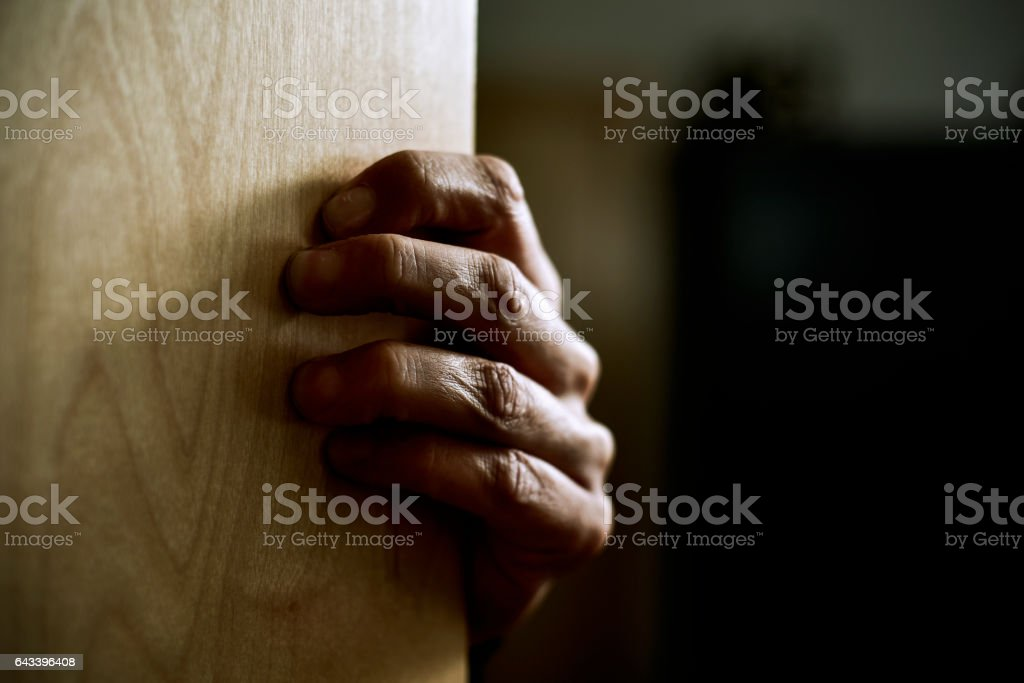 man hand popping out from behind a door stock photo
