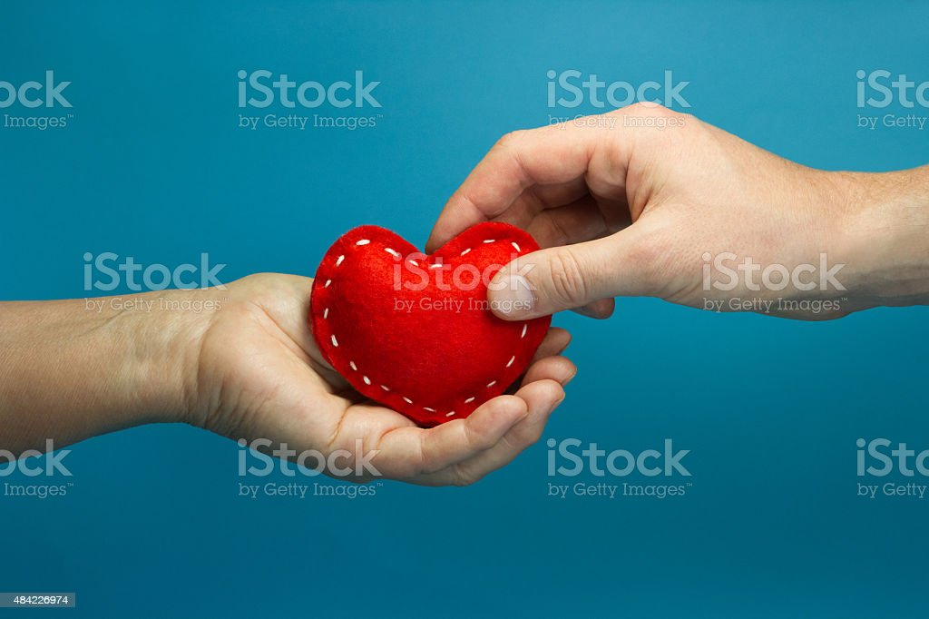Man hand puting the red soft heart in woman hand stock photo