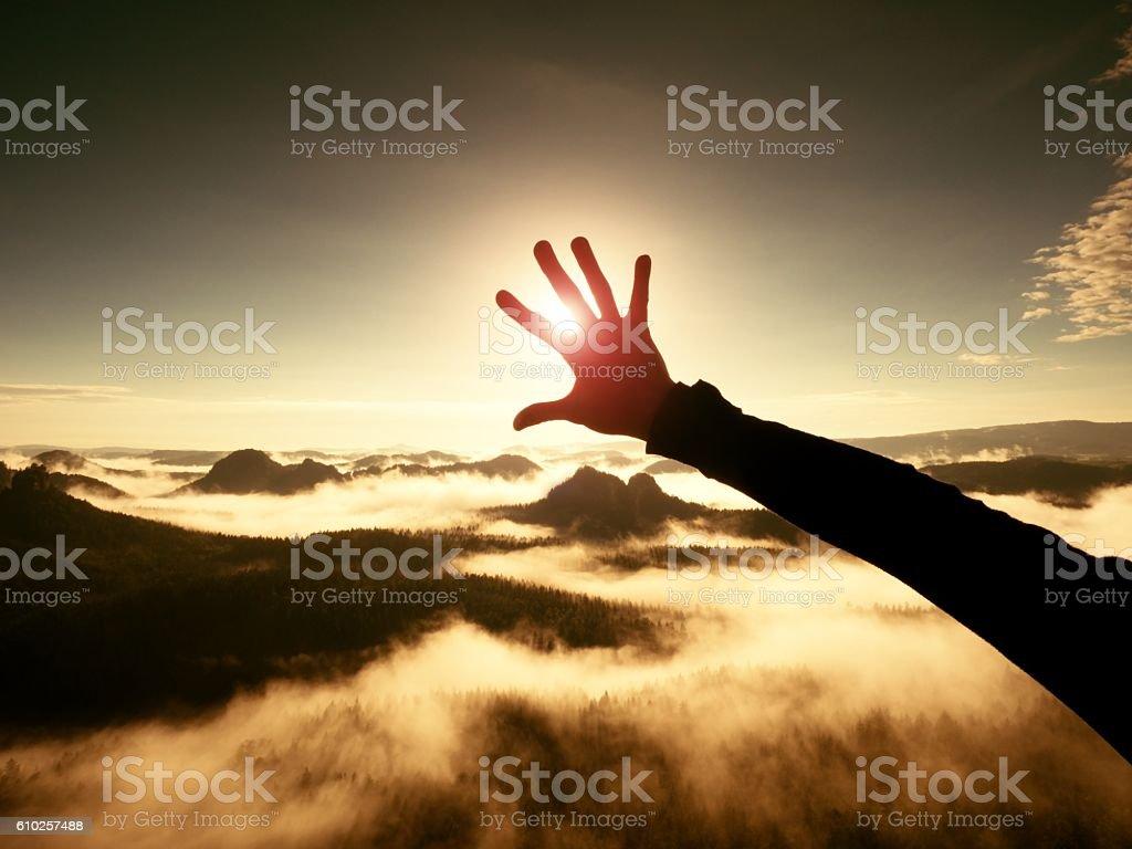 Man hand touch Sun. Misty daybreak in beautiful hilly landscape stock photo
