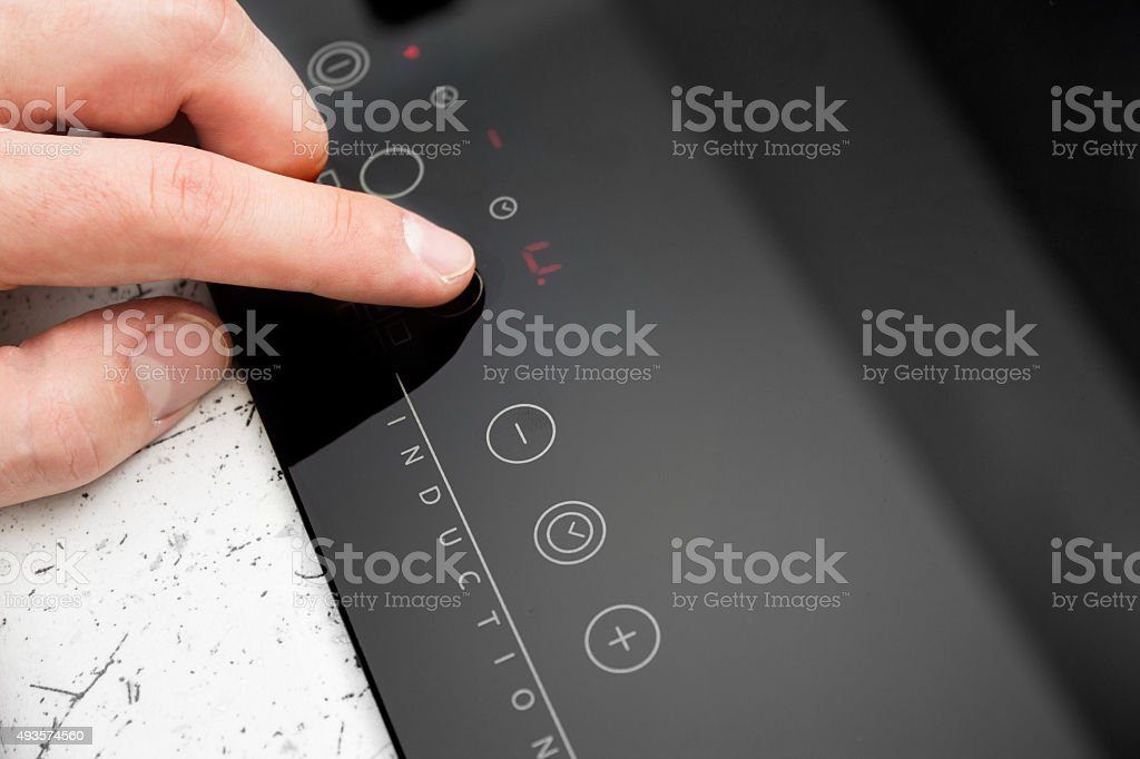 Man hand turns on modern induction cooker stock photo