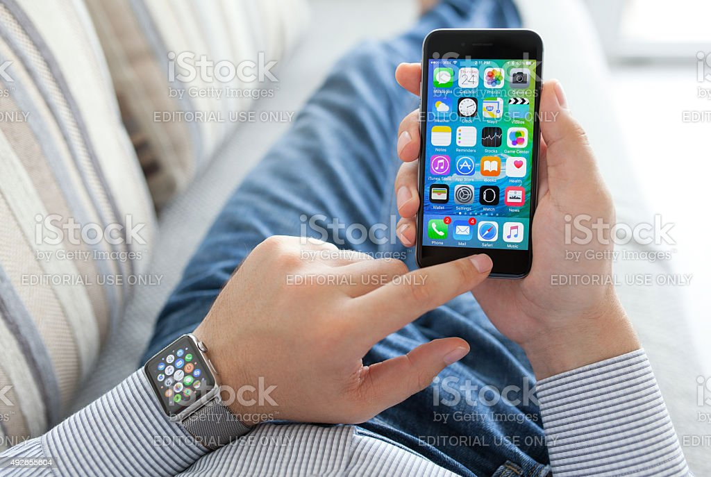 Man hand with Apple Watch holding iPhone stock photo