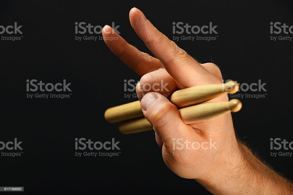 Man hand with drumsticks and devil horns over black royalty-free stock photo