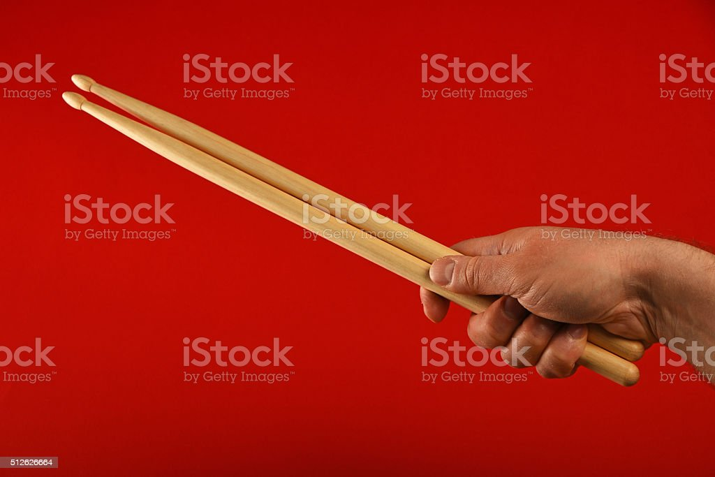 Man hand with drumsticks and devil horns over red royalty-free stock photo