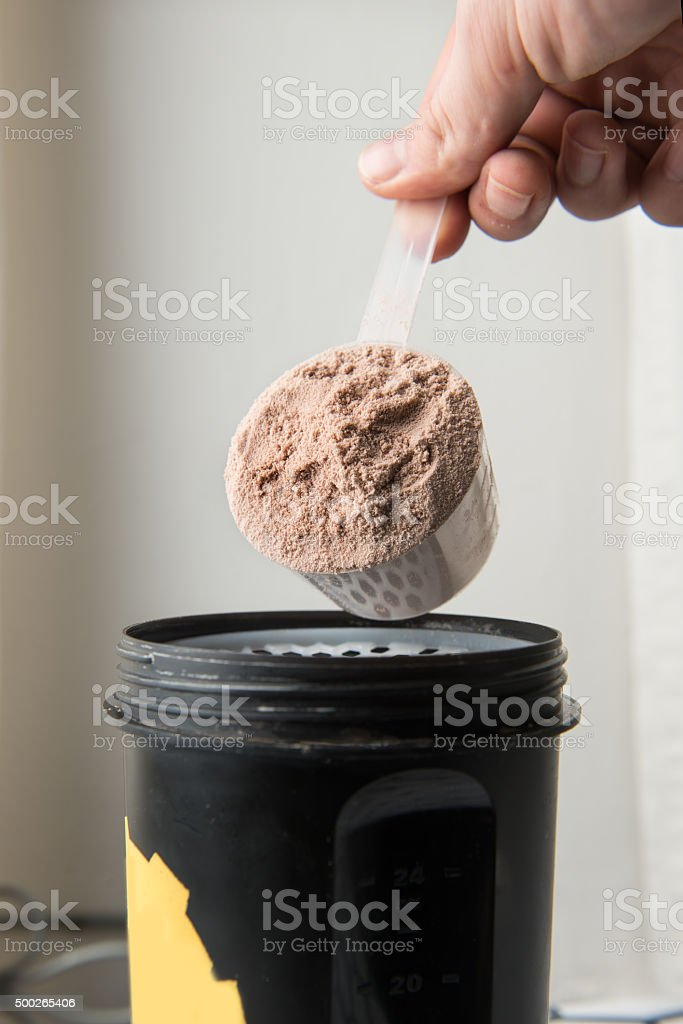 man hand with jar and bottle preparing protein shake stock photo