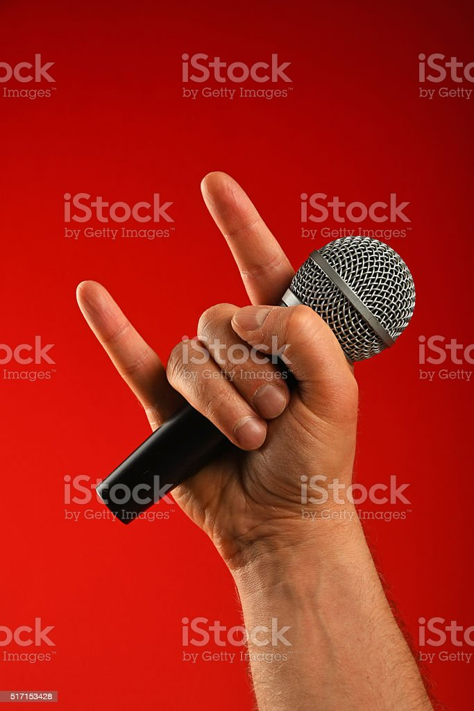 Man hand with microphone and devil horns over red royalty-free stock photo