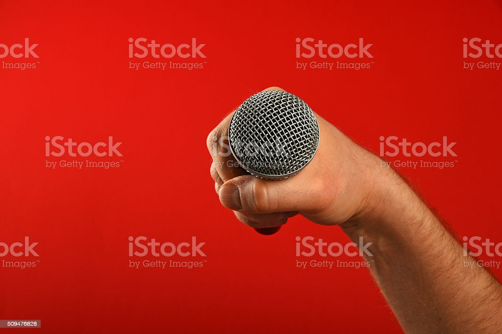 Man hand with microphone over red background royalty-free stock photo