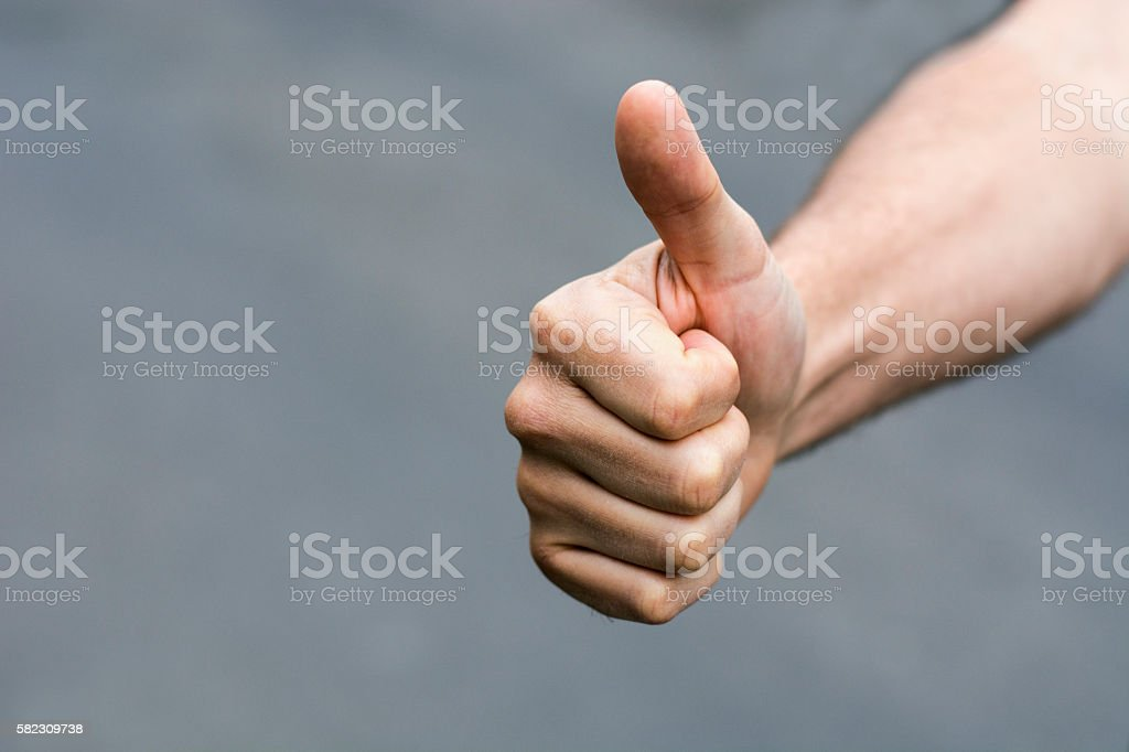 Man hand with thumb up isolated on grey background stock photo