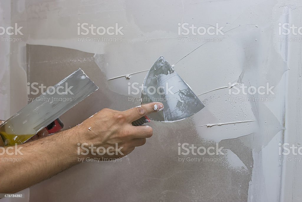 man hand with trowel plastering a wall stock photo