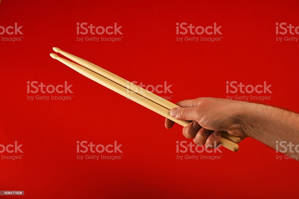Man hand with two drumsticks over red royalty-free stock photo