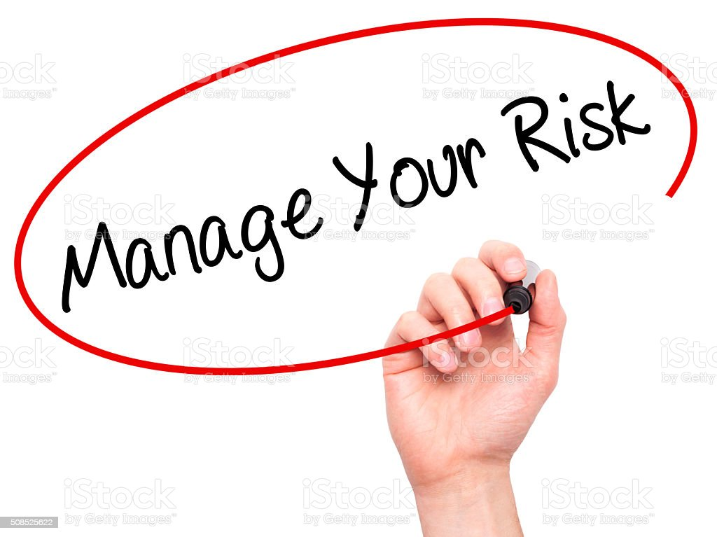Man Hand writing Manage your Risk with black marker stock photo