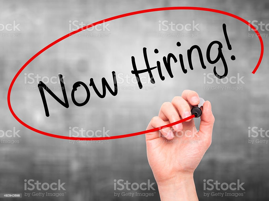 Man Hand writing Now Hiring! with marker stock photo