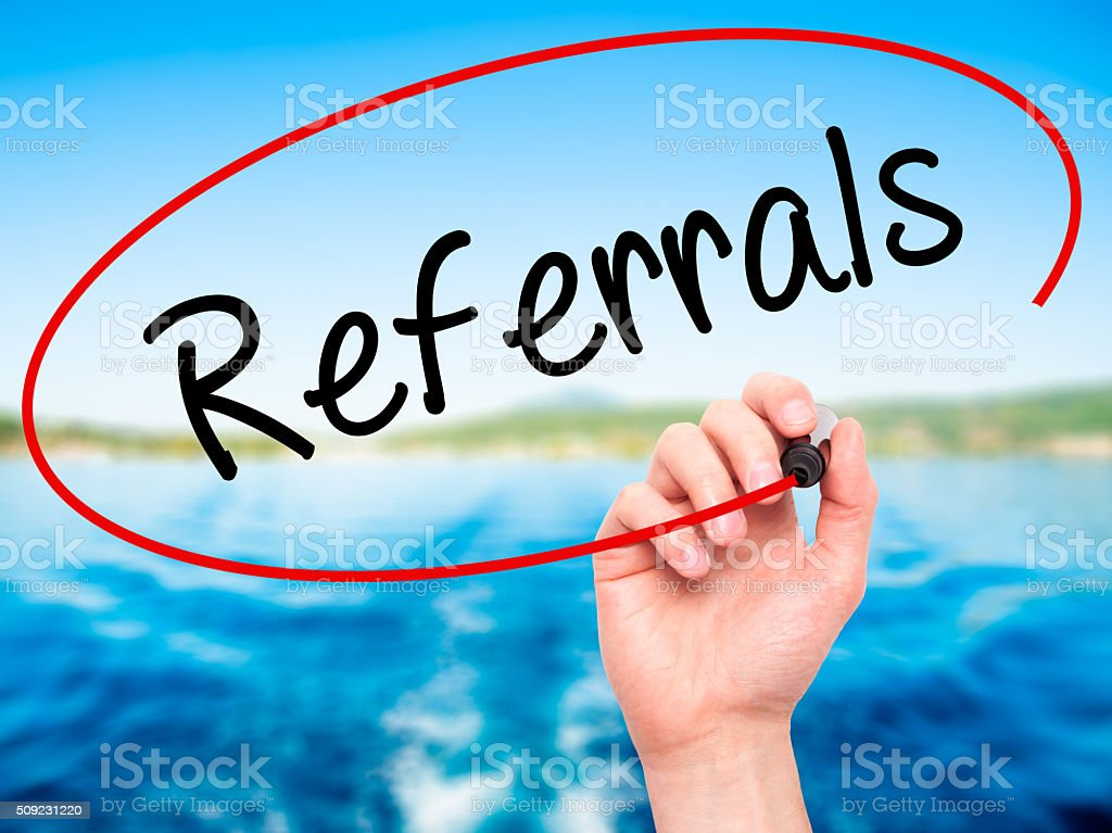 Man Hand writing Referrals with black marker on visual screen. stock photo