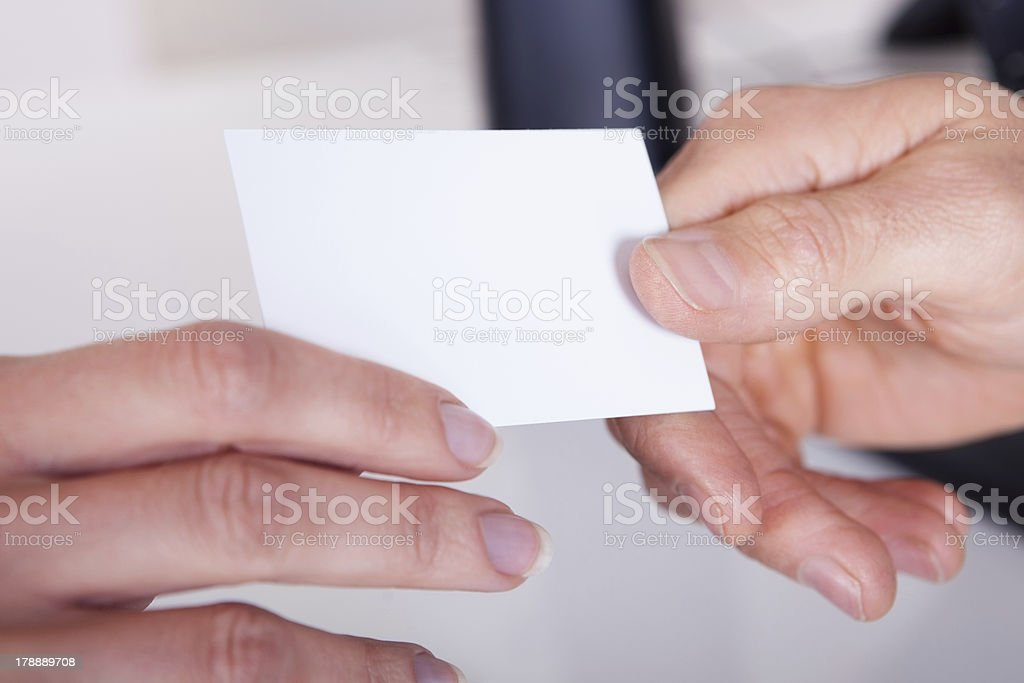 Man handing a woman business card stock photo
