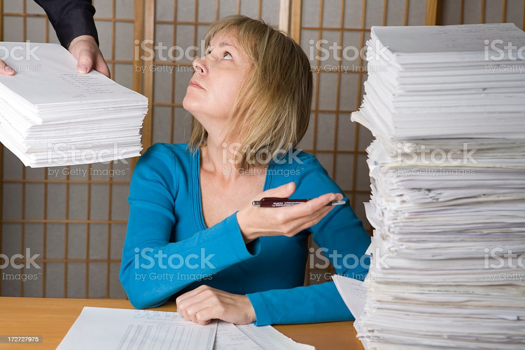 Man handing more paperwork to do to woman seated at desk royalty-free stock photo