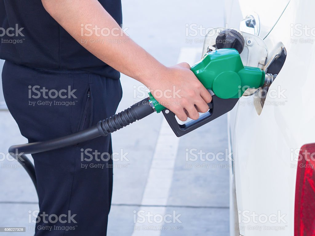 man handle fuel nozzle to refuel.  in gas station. stock photo