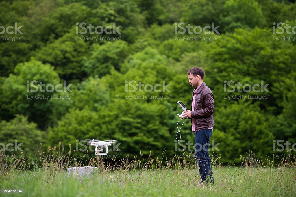 Man handling drone in nature stock photo