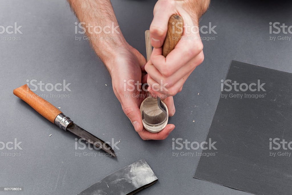 Man hands carving of a wooden spoon with hook knife stock photo