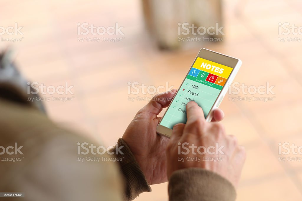 man hands checking shopping list on the screen stock photo