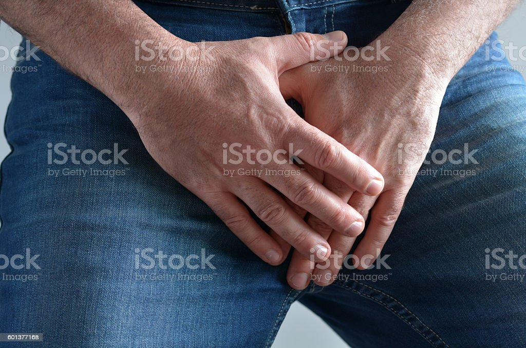 Man hands covering his painful crotch stock photo