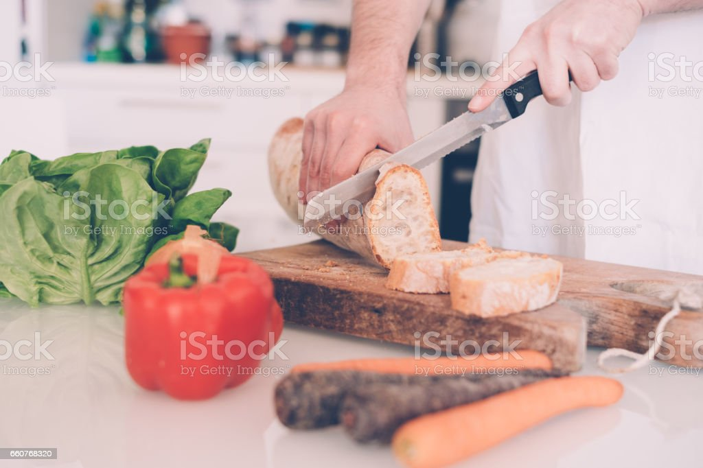 Man hands cutting bread slices in the kitchen stock photo
