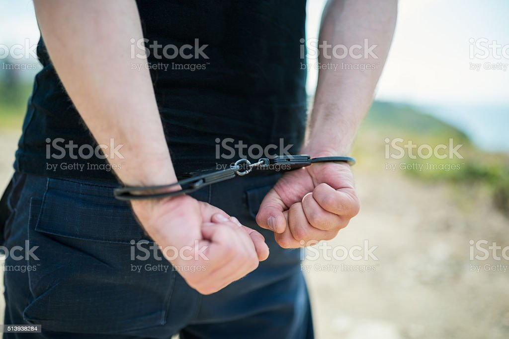 Man hands in handcuffs. stock photo