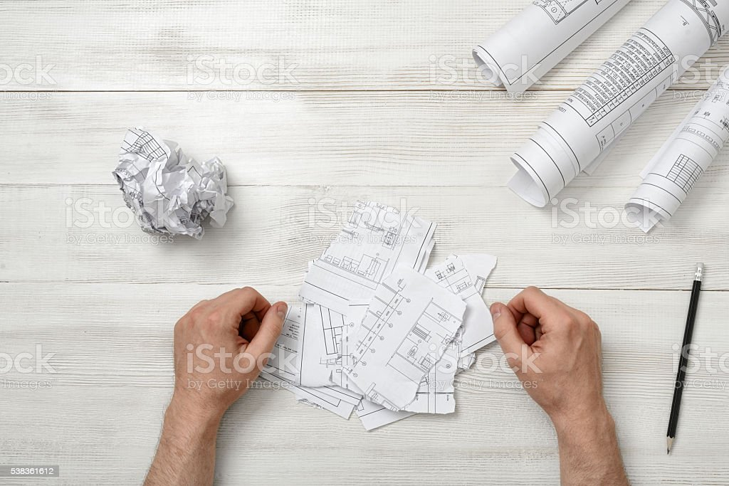 Man hands on wooden table with teared designs and pen. stock photo