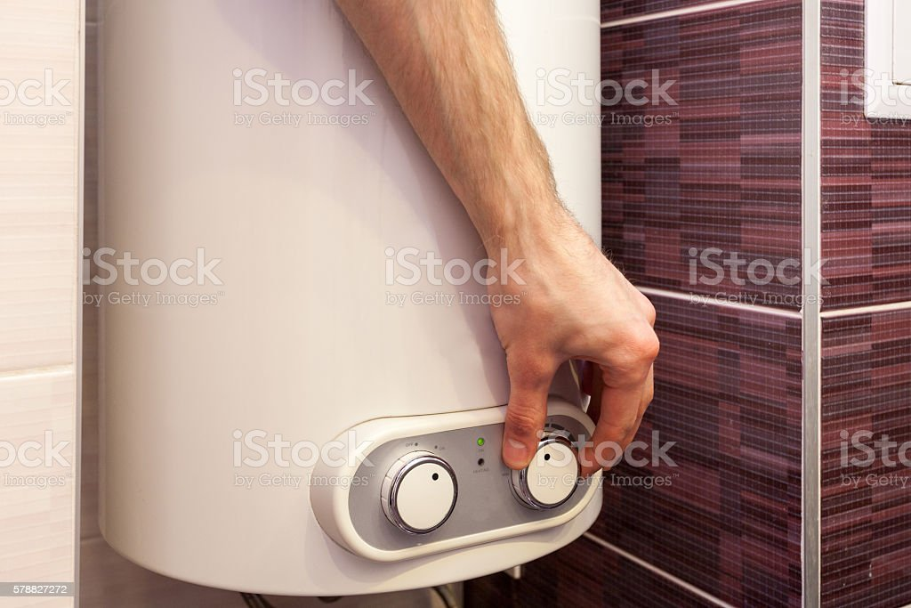 Man hands setting the temperature of water in Electric Boiler stock photo