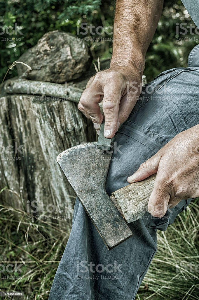 Man Hands Sharpening Rusty Old Axe with Whetstone stock photo