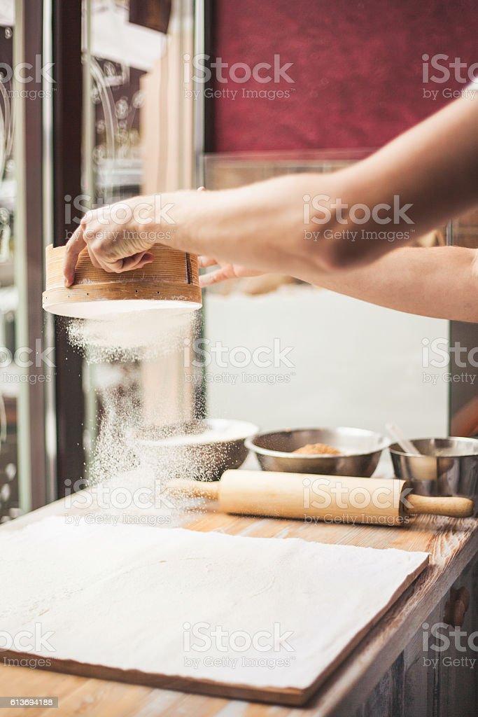 Man hands spilling powder on dough. stock photo