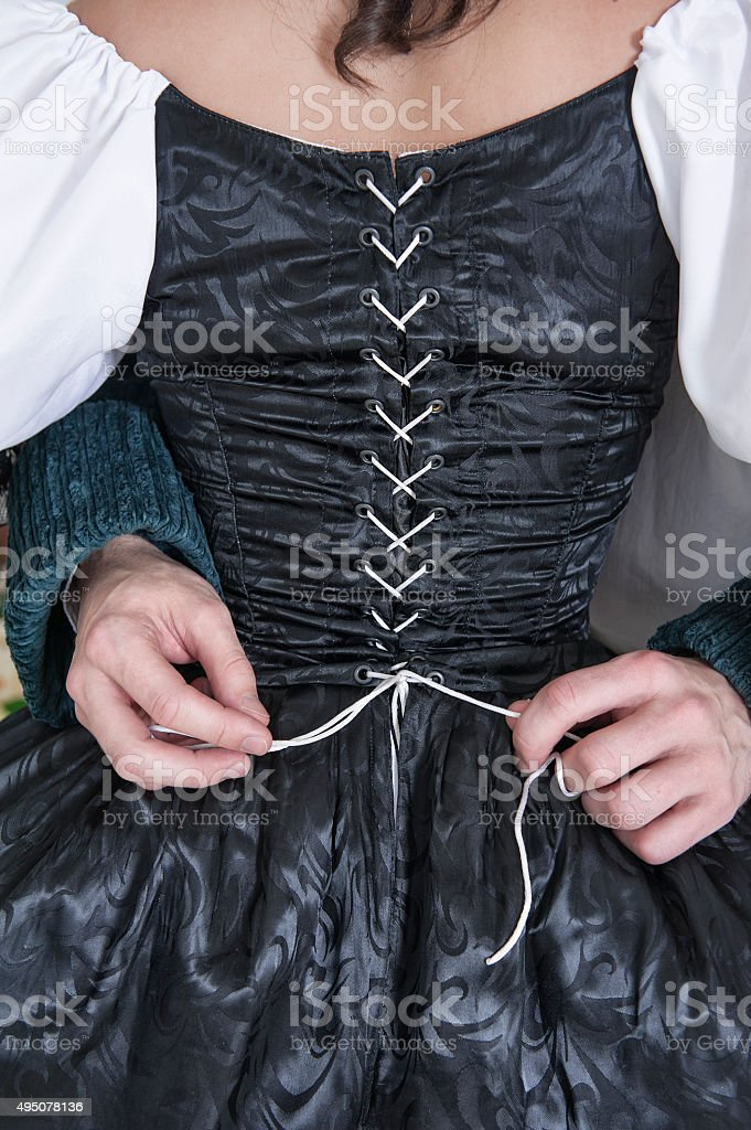 Man hands untying corset of woman in medieval dress stock photo