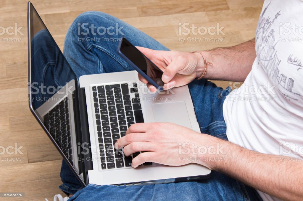 Man hands using laptop and smart phone stock photo