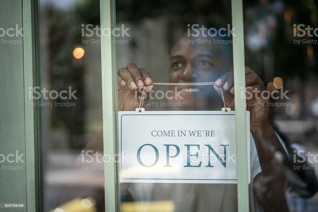 Man hanging an open sign at a restaurant stock photo