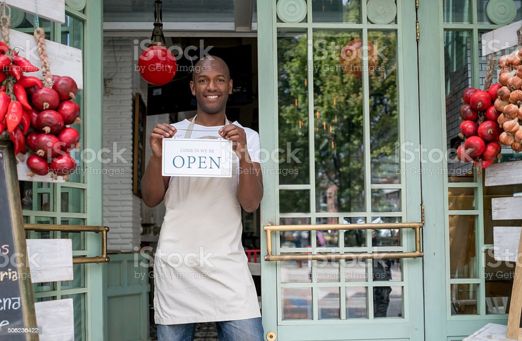 Man hanging open sign at a restaurant stock photo