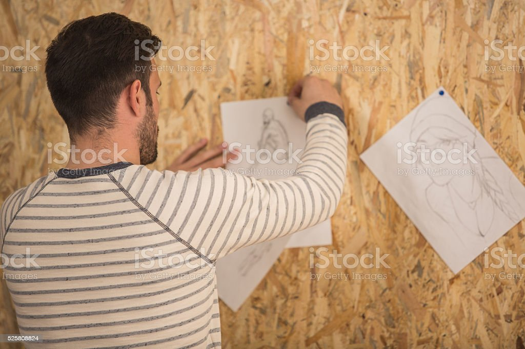 Man hanging pencil drawings on the wall stock photo