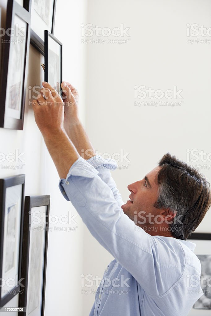 Man Hanging Picture Frames On Wall At Home stock photo