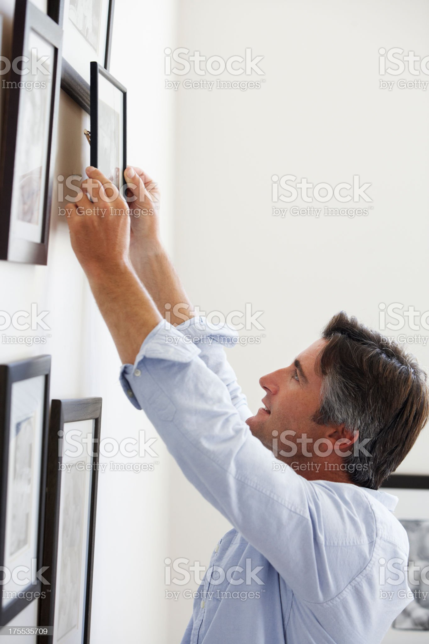 Man Hanging Picture Frames On Wall At Home royalty-free stock photo