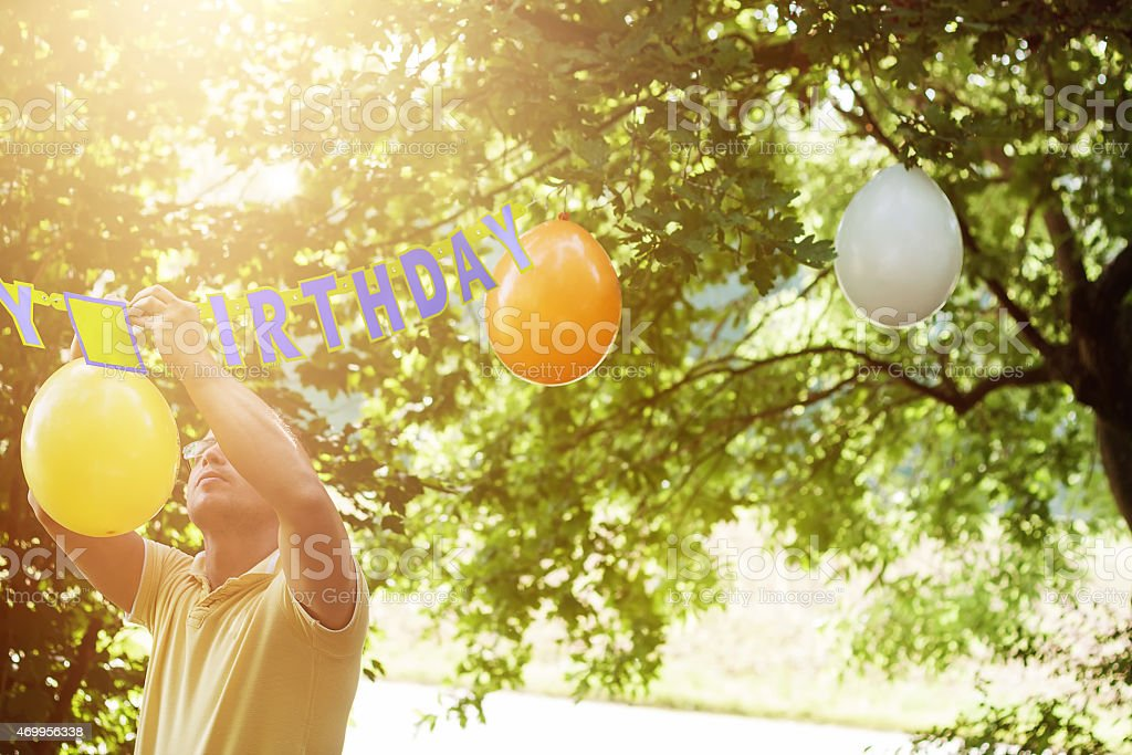 man hanging up ballons to preparing the birthday party stock photo