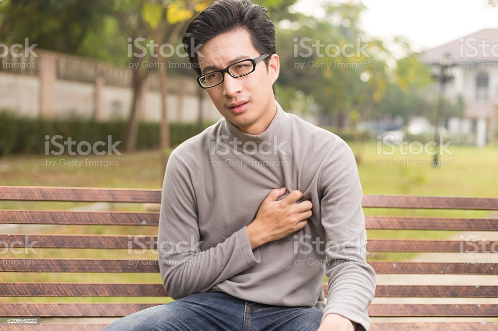 Man has chest pain at park stock photo