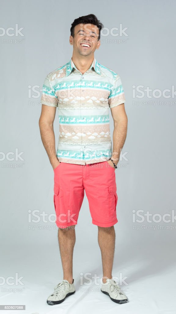 Man has his hands in his pocket and smiles carefree. Handsome brazilian male wearing a colorful shirt. Summer, tropical. 30s. Fit and athletic. stock photo