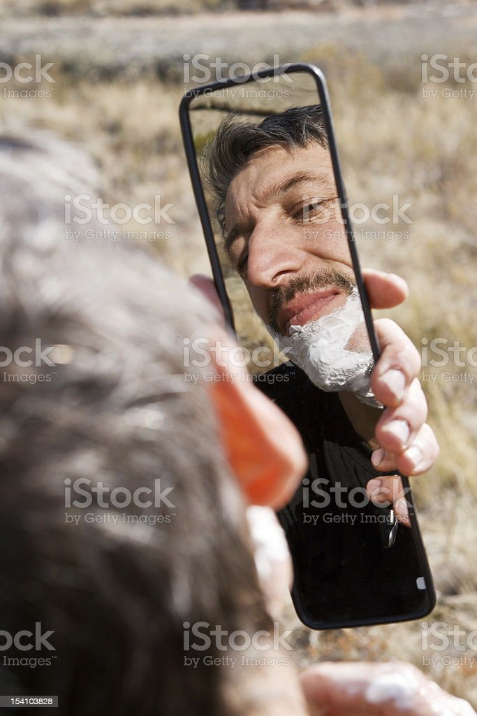 Man has shave looking in automobile mirror stock photo