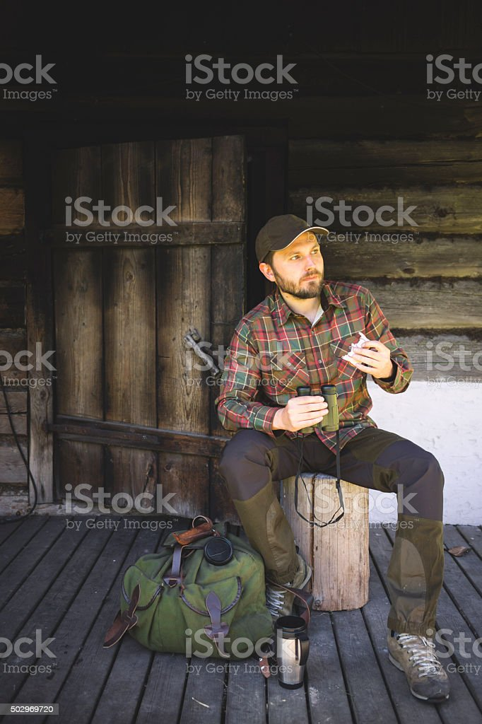 Man Having a Break at a Countryside House After Hiking stock photo