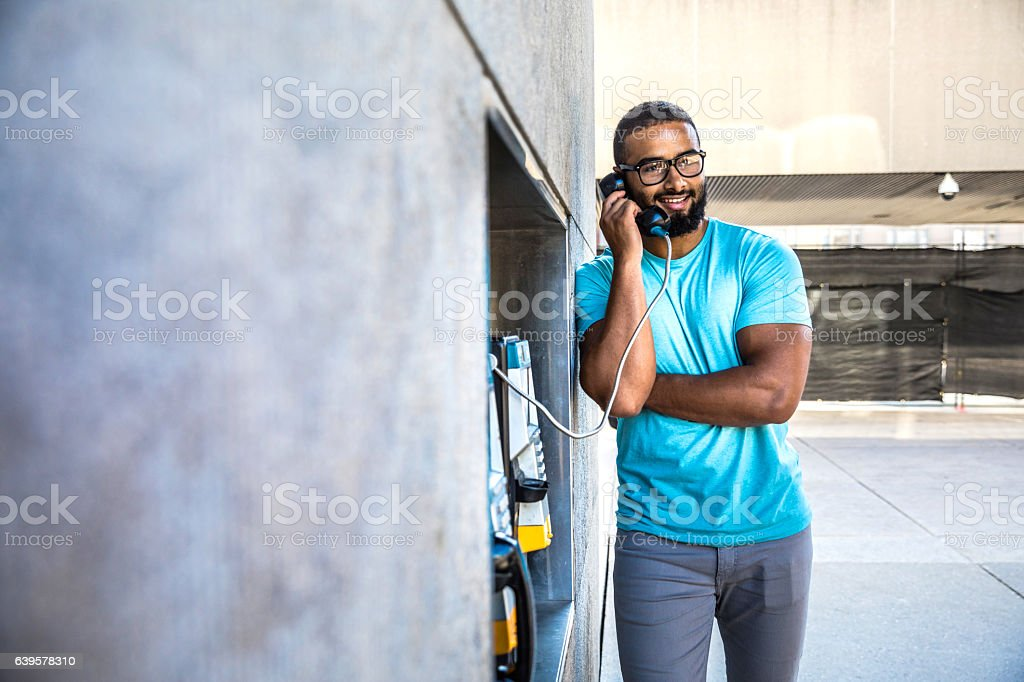 Man having a call on a phone booth in downtown stock photo
