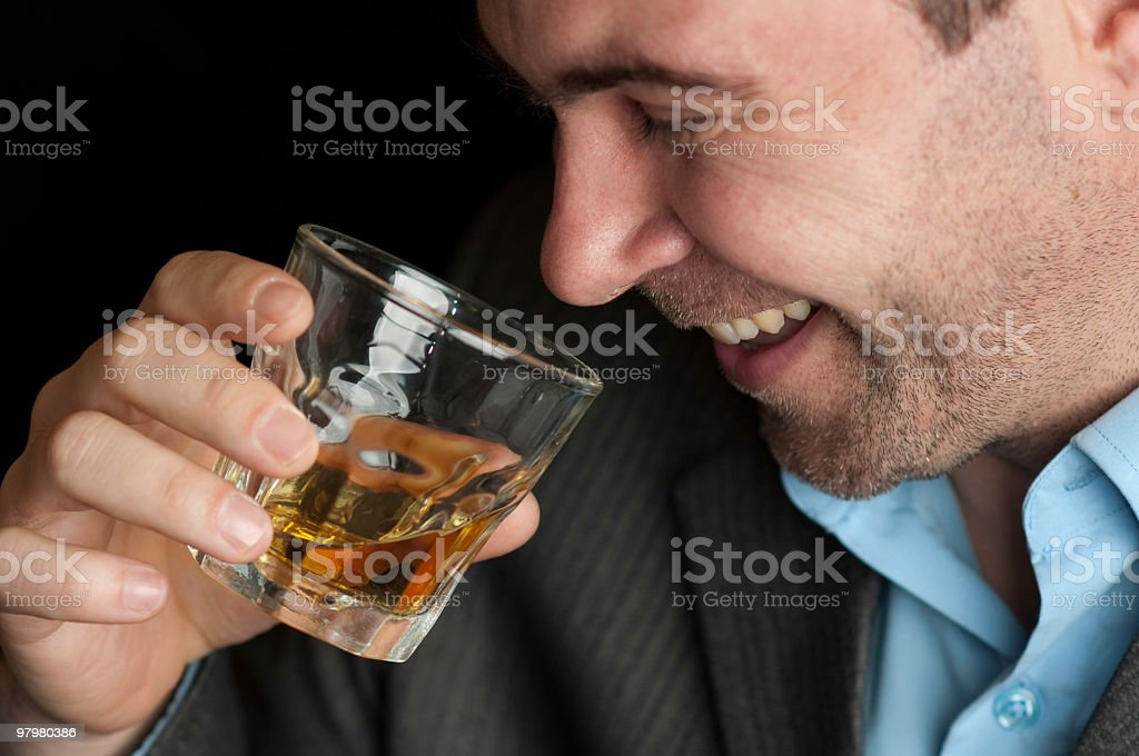 A man having a good time drinks whiskey from a glass stock photo