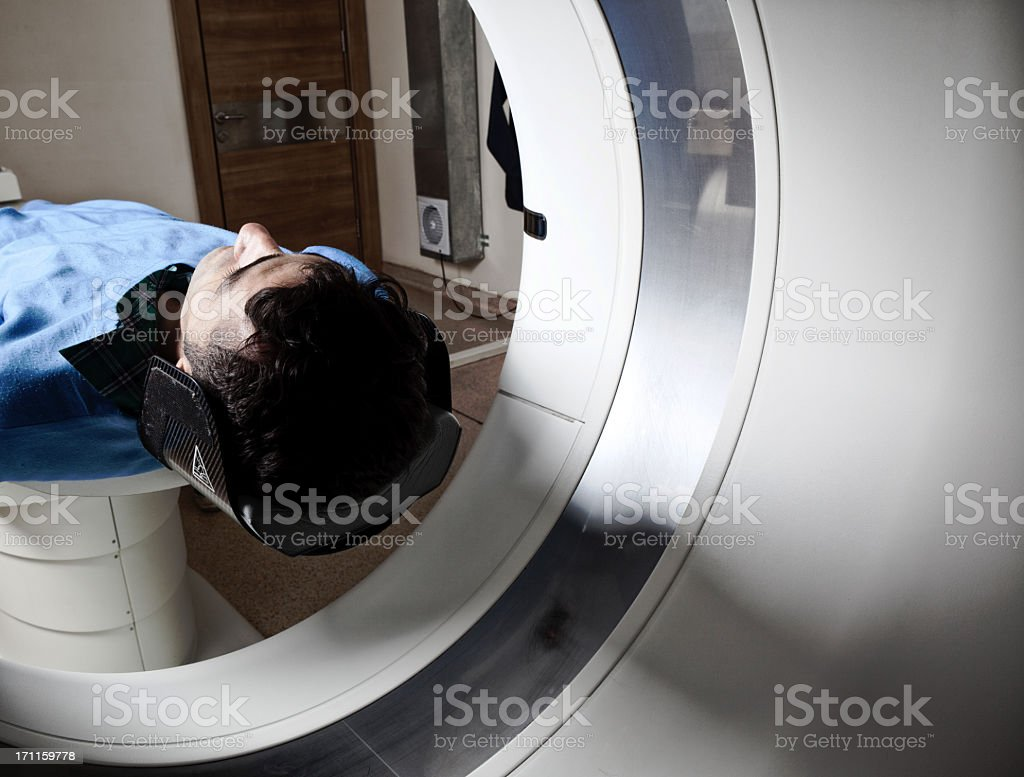 Man having a medical examination via CAT scanner stock photo