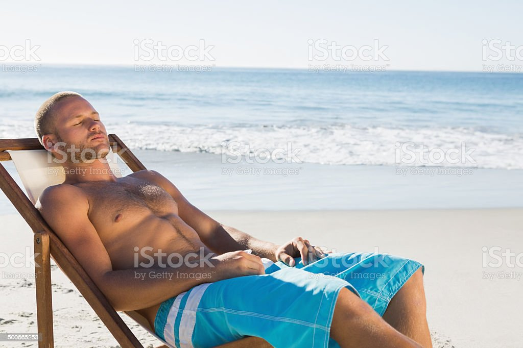 Man having a nap while sunbathing on his deck chair stock photo