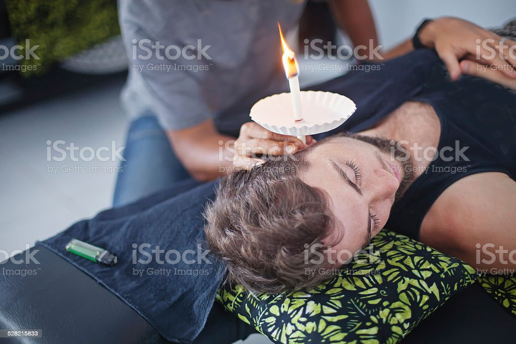 man having an ear candle therapy stock photo