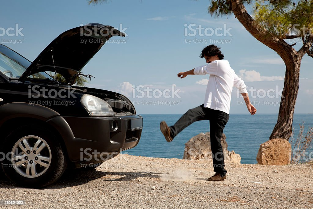 Man having car problems kicking dirt in frustration stock photo