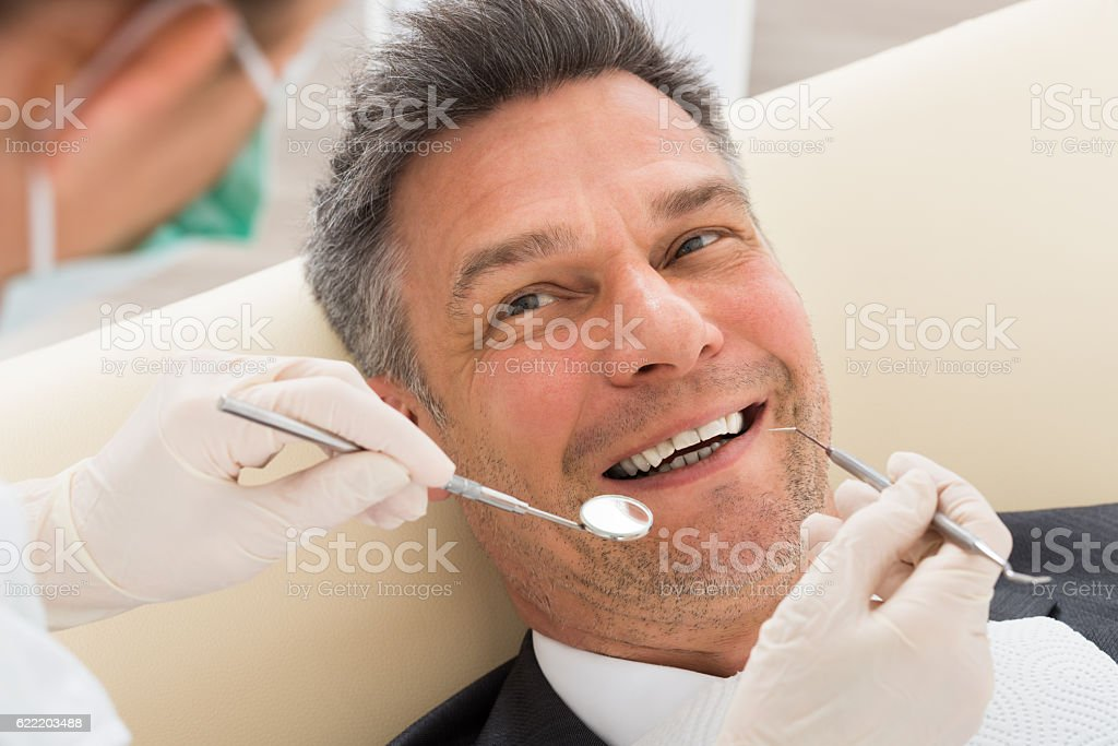 Man Having Dental Check-up In Clinic stock photo
