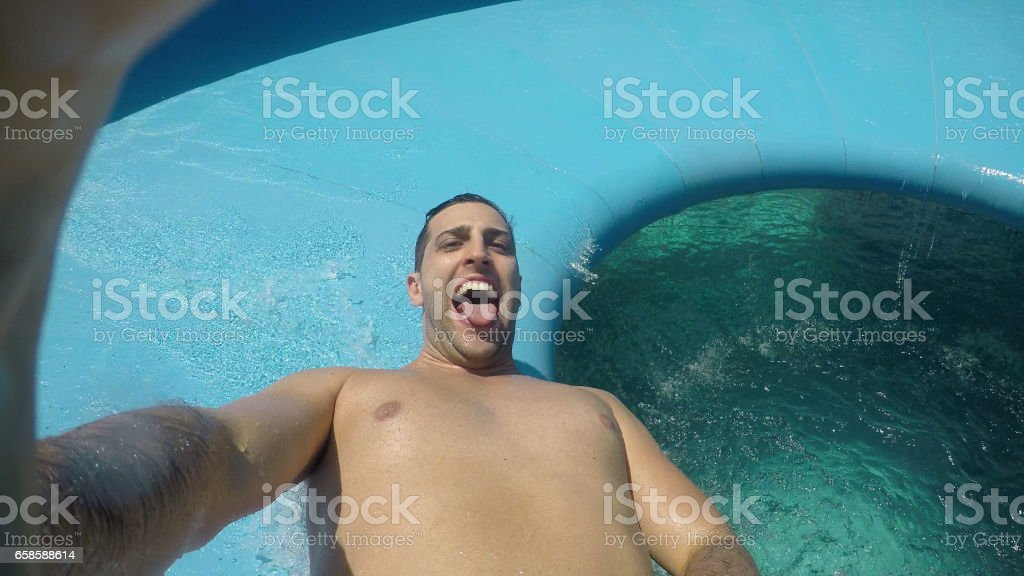 Man having fun and sliding down in a water slide stock photo