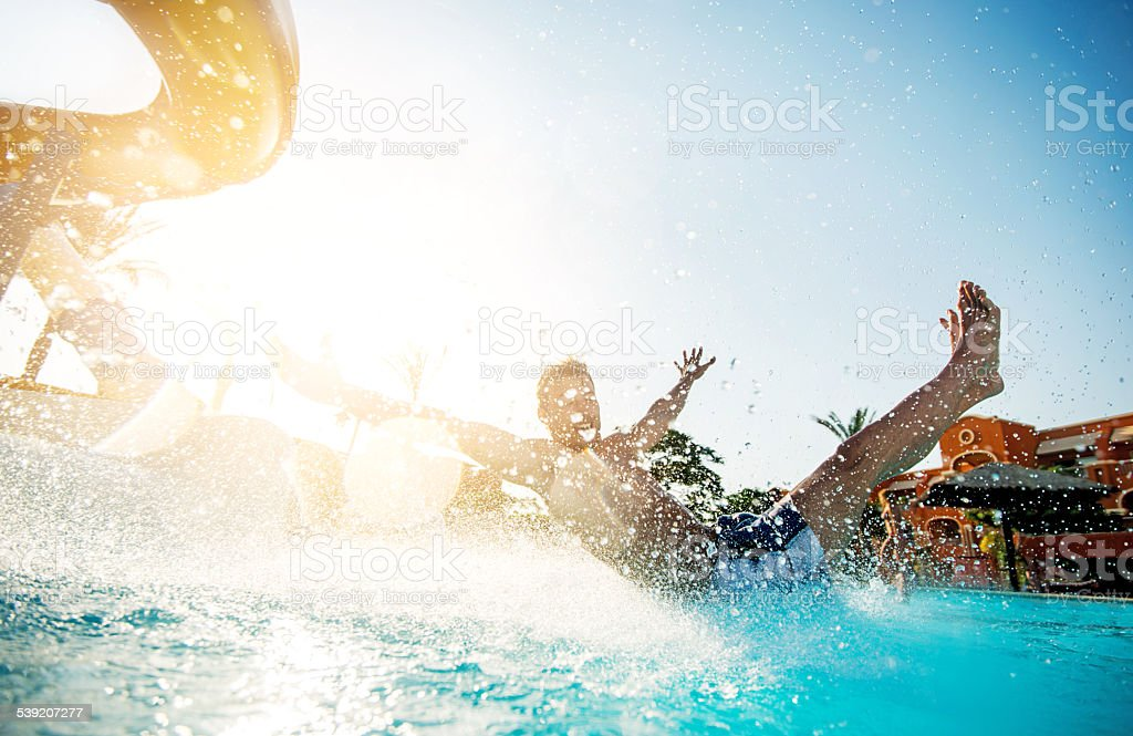 Man having fun on water slide. stock photo